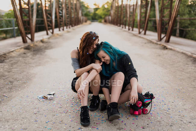 Girls sitting on skateboard and laughing — Stock Photo