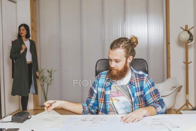 Retrato del hombre sentado en el lugar de trabajo mientras que la mujer viene en la oficina. - foto de stock