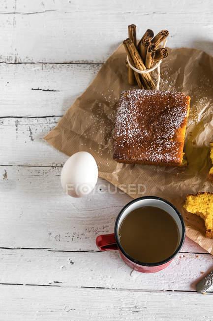 Vista piatta di torta al limone su carta da forno e tazza di cioccolata calda sulla tabella bianca rurale con l'uovo — Foto stock