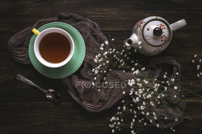 Cup of tea and teapot with wildflowers on brown surface — Stock Photo