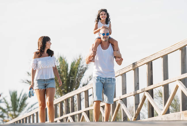 Smiling family with daughter sitting on father's shoulders walking along bridge in sunlight. — Stock Photo