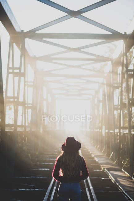 Menina andando na ponte iluminada pelo sol . — Fotografia de Stock