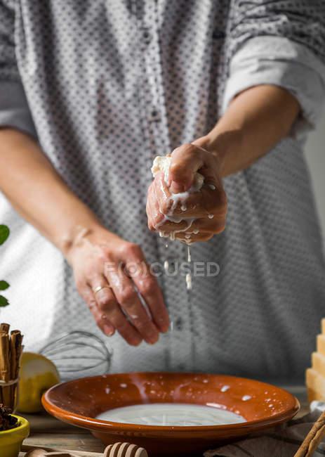 Средняя часть самки отжимает кусок хлеба из сладкого молока — стоковое фото