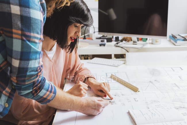 Vista lateral de arquitectos masculinos y femeninos discutiendo el plano en la oficina - foto de stock