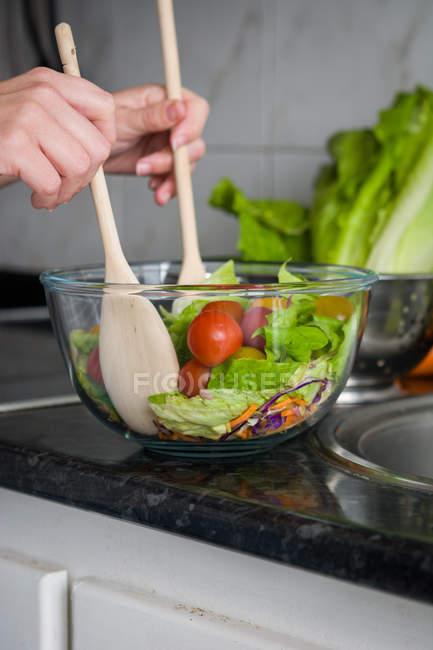 Кадроване зображення руки, змішування салат в миску на кухонного столу — стокове фото