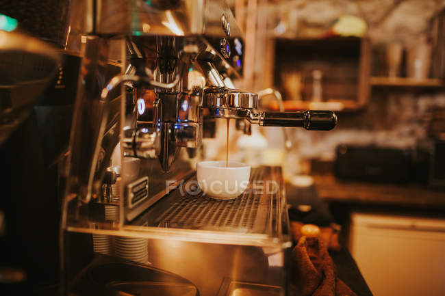 Coffee maching pouring cofee in white cup — Stock Photo