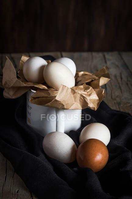Stillleben mit Eiern im Becher auf Handtuch am Tisch — Stockfoto