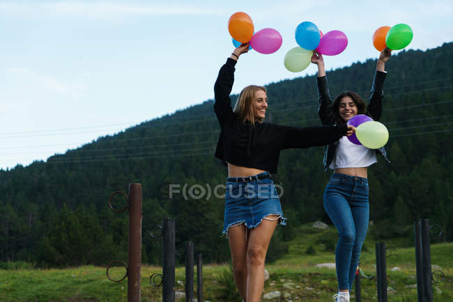 Festive women running with balloons at nature — Stock Photo