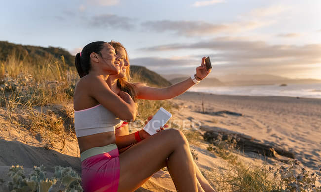 Femmes fitness assis sur le sable et de faire selfie — Photo de stock