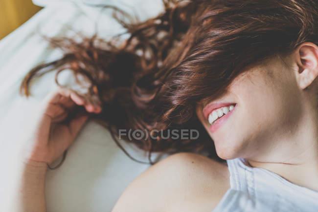 Donna sorridente con il viso coperto di capelli rossicci — Foto stock