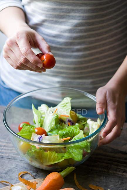 Midsection della donna aggiungendo pomodoro ciliegia in ciotola con insalata — Foto stock