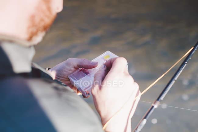 En vista del hombro del hombre preparando anzuelos para la pesca - foto de stock