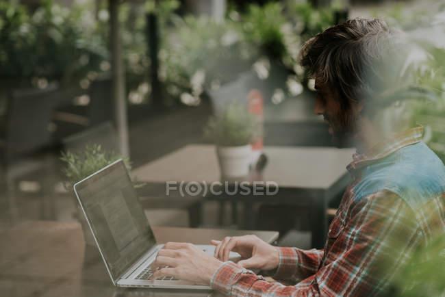 Вид збоку бородатого мужчини, сидячи на терасі кафе таблиці та за допомогою ноутбука — стокове фото