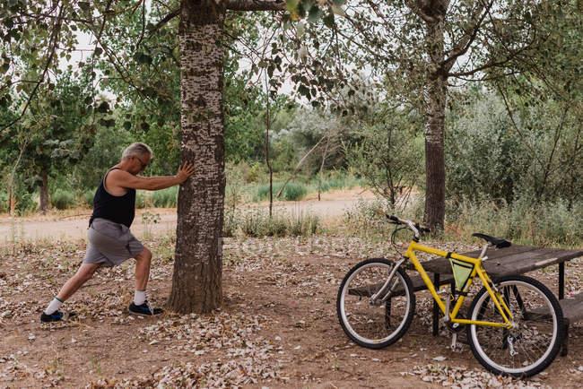 Vista lateral do homem idoso esticando o corpo no parque antes da bicicleta — Fotografia de Stock