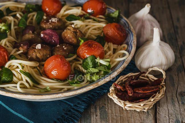 Nahaufnahme von Spaghetti mit Fleischbällchen, Cherry-Tomaten und Basilikum auf Holztisch mit kleinen Korb mit Paprika und Knoblauch — Stockfoto