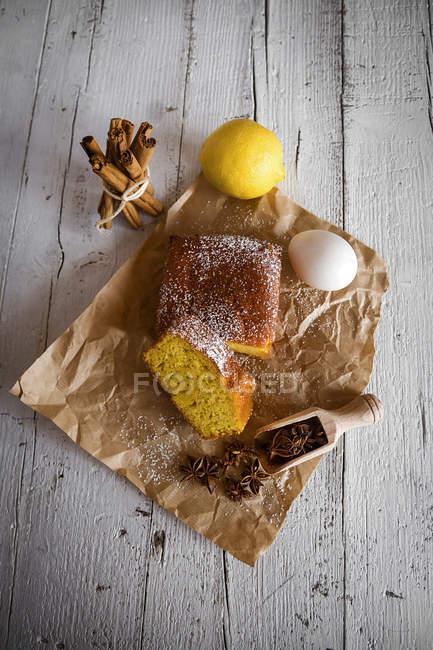 Vista piatta di torta al limone con ingredienti il panificio carta sopra tabella rurale bianca — Foto stock