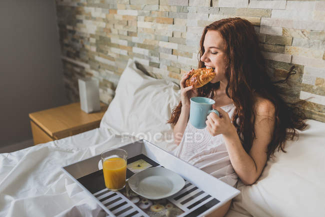 Girl eating croissant with cup of coffee in bed — Stock Photo