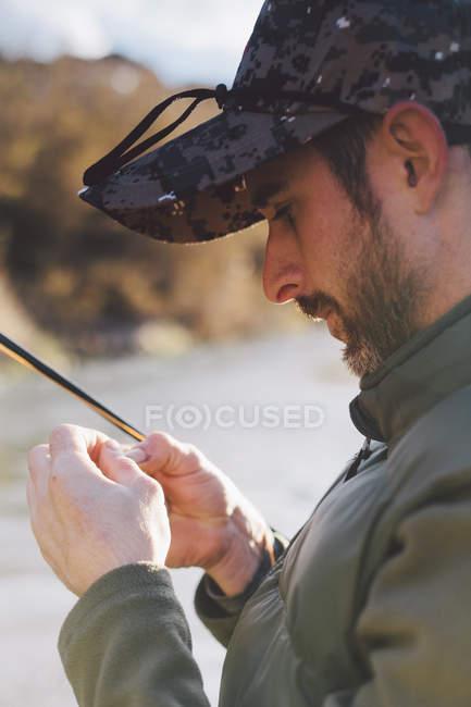 Retrato de hombre sereno preparando anzuelo para la pesca en el río - foto de stock
