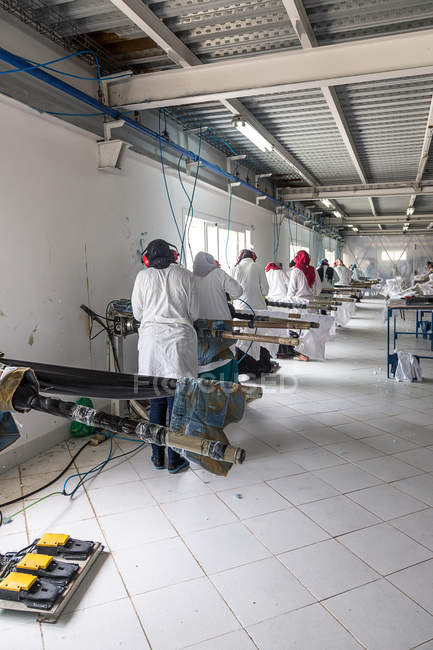 TANGIER, MARRUECO- 18 de abril de 2016: Máquinas y maquinistas industriales de hierro trabajando en línea - foto de stock