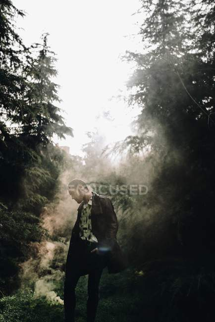 Portrait of man standing in smoke among woods and looking down — Stock Photo