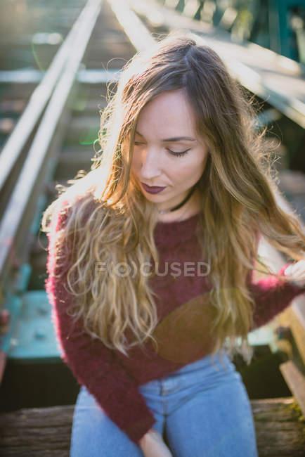 Mädchen sitzt auf Bahnschwelle — Stockfoto
