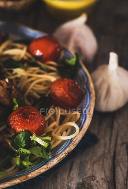Обрізати зображення тарілці повному макарони з базиліком і помідорів чері на сільському дерев'яний стіл з часником — стокове фото
