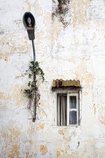 White shabby facade with small window and lantern — Stock Photo