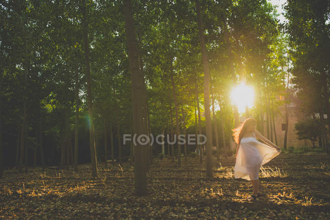Portrait of girl with long red hair wearing long white dress posing at sunlit woods — Stock Photo