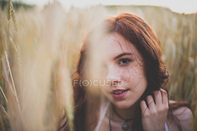 Close up portrait of girl with red hair posing in rye field and looking at camera — Stock Photo