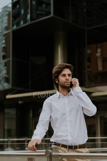 Портрет в белой рубашке говорить через смартфон и глядя в сторону на городской сцене уверен бизнесмен — стоковое фото