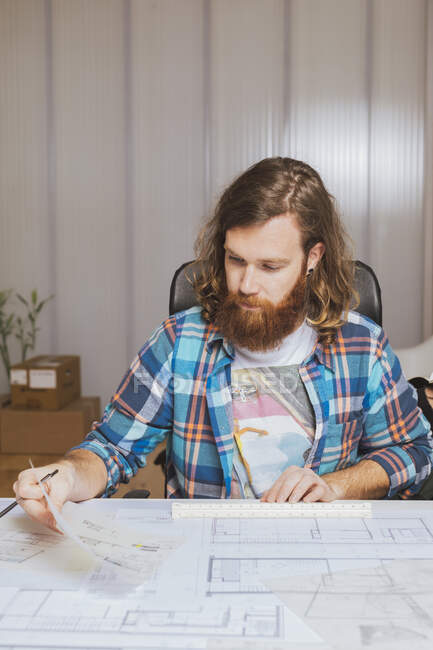 Portrait of bearded man in check shirt sitting at workplace and with blueprints in office. — Stock Photo
