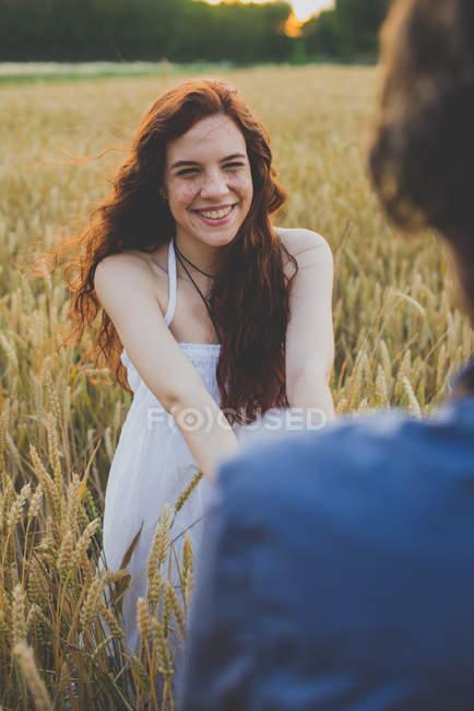 Портрет счастливой рыжеволосой девушки, держащей парней за руки на ржаном поле — стоковое фото