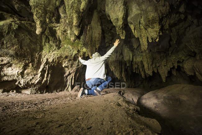 Задній вид людини з підвищеною озброєння в печеру — стокове фото