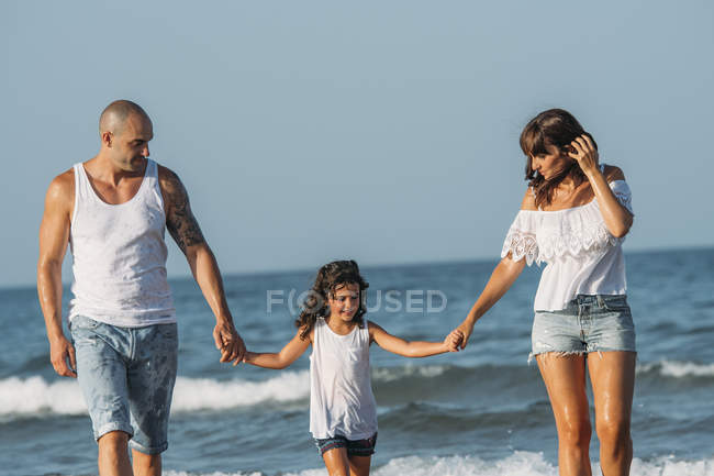 Портрет родини ходьба на пляжі і тримаючись за руки. — стокове фото