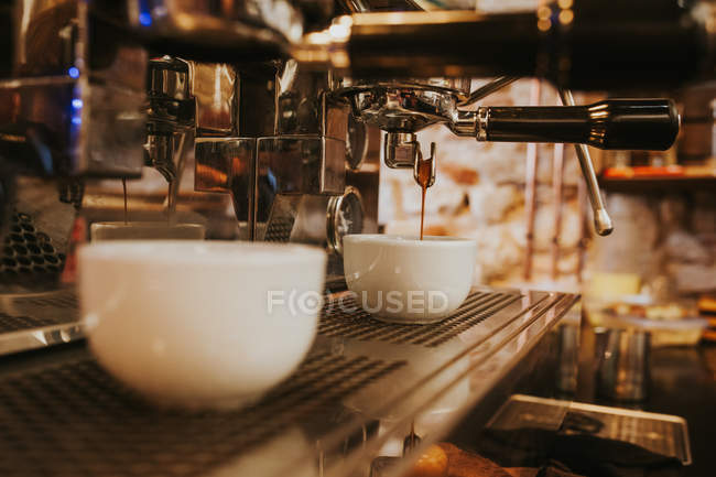 Close up view of coffee machine pouring coffee in white cup — Stock Photo