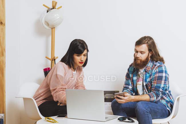 Homme et femme utilisant un ordinateur portable — Photo de stock