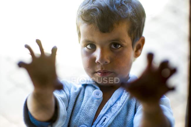 Arabo ragazzo guardando fotocamera e tenendo griglia — Foto stock