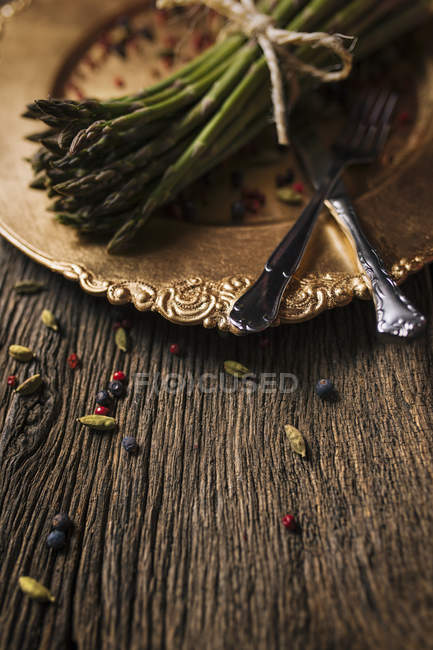 Old golden dish with green asparagus on dark wood — Stock Photo
