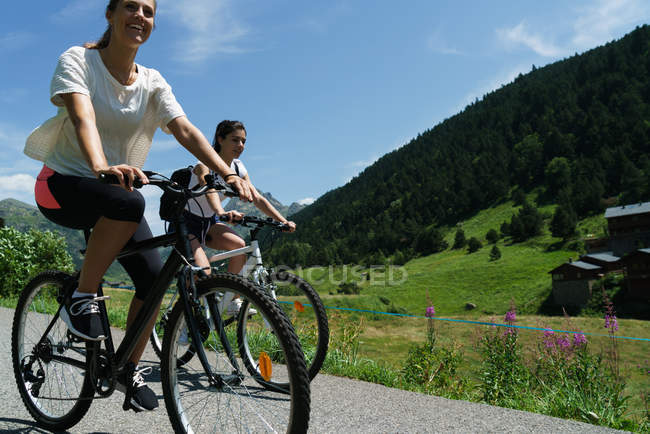 Sporty girls riding bicycles at mountain countryside — Stock Photo