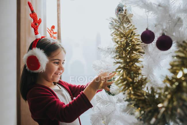 Vista laterale della ragazza felice che porta pelliccia paraorecchie con i antlers immissione Bagattelle sul albero di Natale decorativo — Foto stock