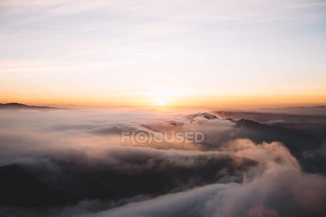Vista aérea del paisaje nuboso en las montañas al atardecer - foto de stock
