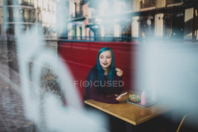Retrato de menina com cabelo azul, sentado à mesa de café com smartphone e desviar o olhar — Fotografia de Stock