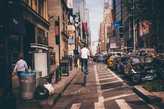 Vista trasera del hombre montando una bicicleta en la calle estrecha de la ciudad - foto de stock