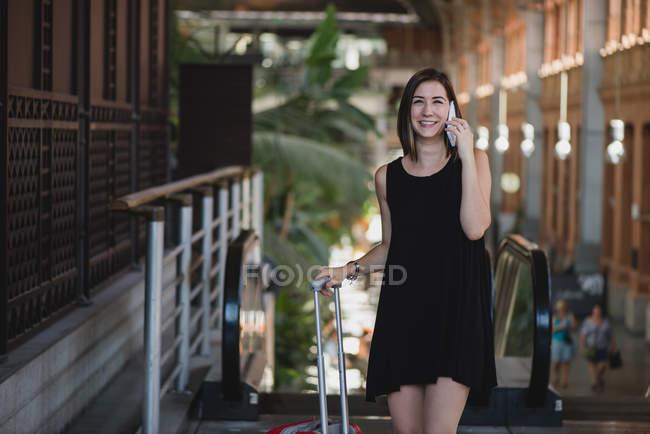 Muy sonriente que lleva maleta roja chica sobre ruedas y hablando por teléfono en la estación - foto de stock