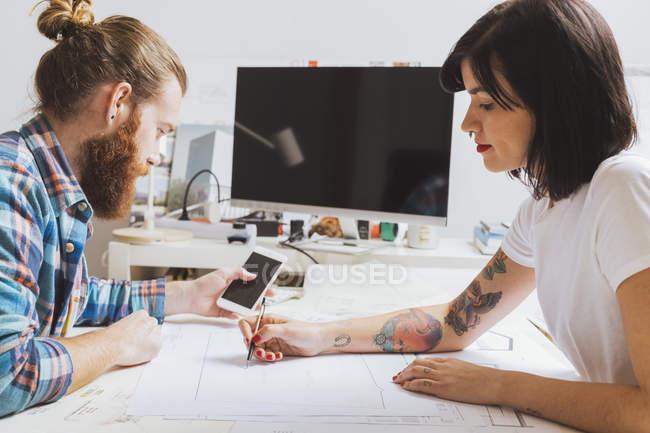 Uomo utilizzando smartphone mentre donna disegno — Foto stock