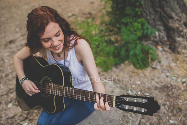 Retrato de ángulo alto de niña pecosa sonriente sentada en el rock y tocando la guitarra - foto de stock