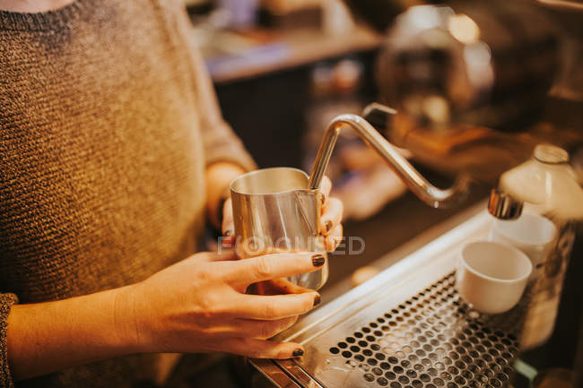 Crop hands beating up cream for cappuccino with coffee machine steamer — Stock Photo