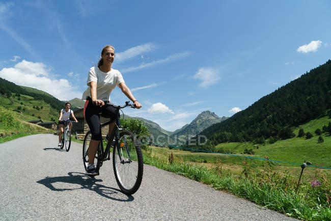 Mulheres andando de bicicleta no campo — Fotografia de Stock