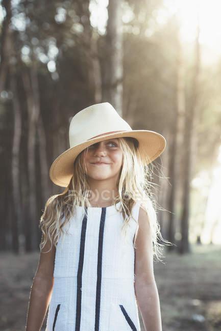 Affascinante ragazza in posa con cappello alla luce del sole — Foto stock