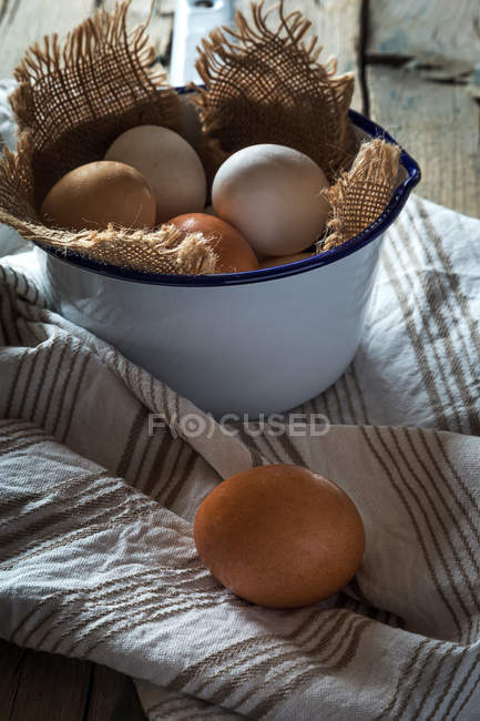 Eggs in metal bowl  on rural table — Stock Photo